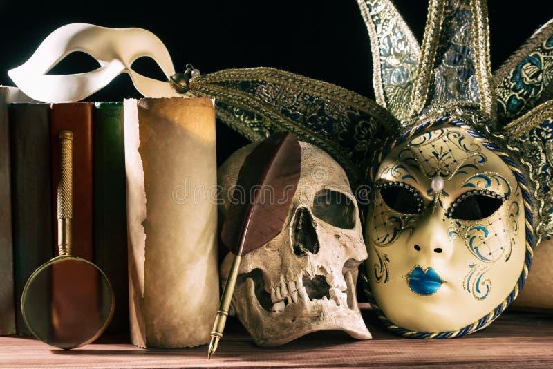 Theater- und Dramakonzept Menschlicher Schädel, venetianische Masken mit alter Rolle, Bücher, Lupe und Spule auf Holztisch lizenzfreie stockbilder