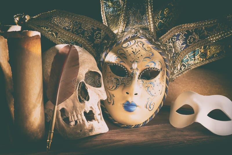 Theater- und Dramakonzept Menschlicher Schädel, venetianische Masken mit alter Rollenspule auf Holztisch stockfotos