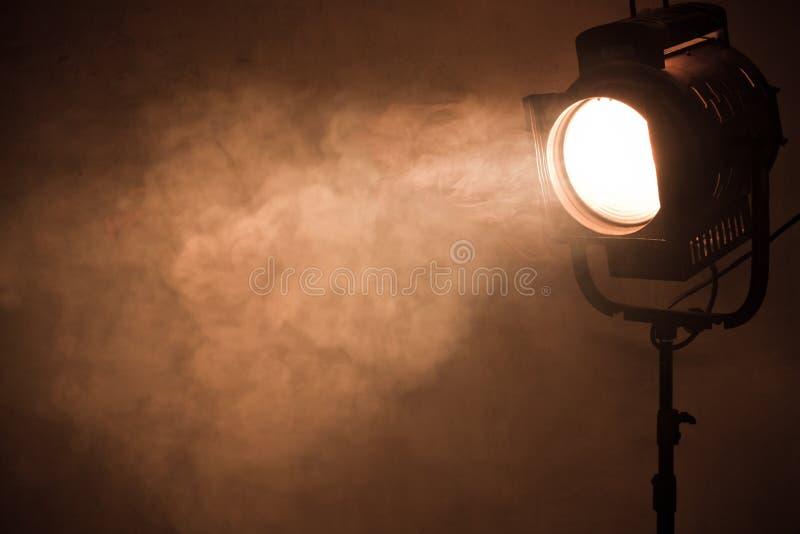 Theaterscheinwerferlicht mit Rauche gegen Schmutzwand stockfoto