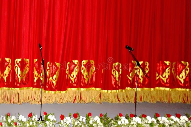 Theatraal rood fluweelgordijn met gouden patroon, en de microfoons royalty-vrije stock foto