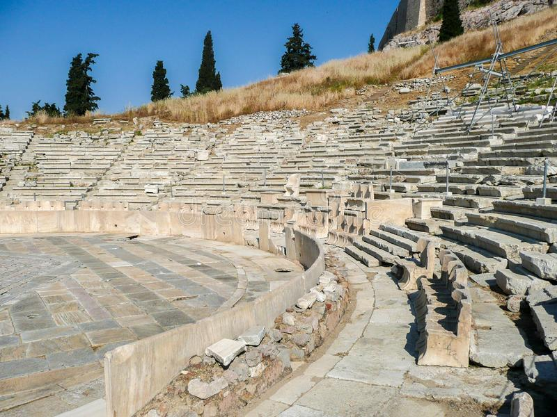 The Theatre of Dionysus Eleuthereus of the Athenian Acropolis. Athens, Greece. Ancient greek amphitheater. old ruins, spectators` or VIPs seats at the first stock photo