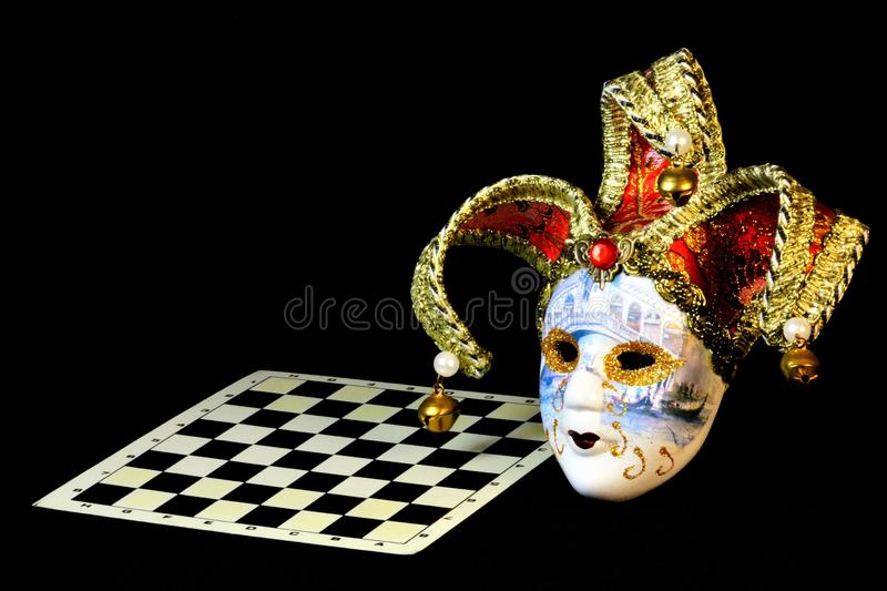 Theatrical carnival mask and chess Board. The mask is a symbol of transformation, change and mystery, real to desired. The aspect. Of transformation peculiar to stock image