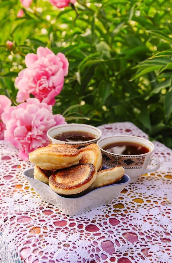 Thee in de stijl van het land in de zomertuin Twee koppen zwarte thee en pannekoeken op met de hand gemaakt gehaakt uitstekend ka royalty-vrije stock foto