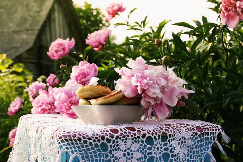 Thee in de stijl van het land in de zomertuin Twee koppen zwarte thee en pannekoeken op met de hand gemaakt gehaakt uitstekend ka royalty-vrije stock afbeelding