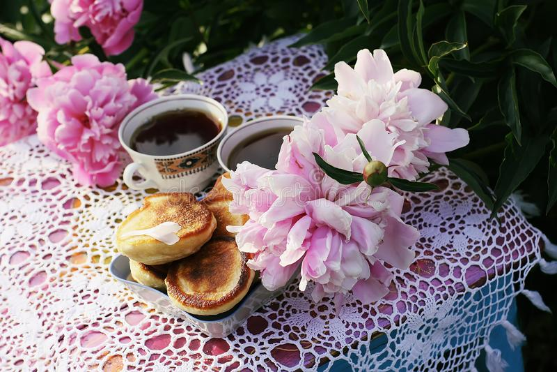 Thee in de stijl van het land in de zomertuin Twee koppen zwarte thee en pannekoeken op met de hand gemaakt gehaakt uitstekend ka royalty-vrije stock fotografie