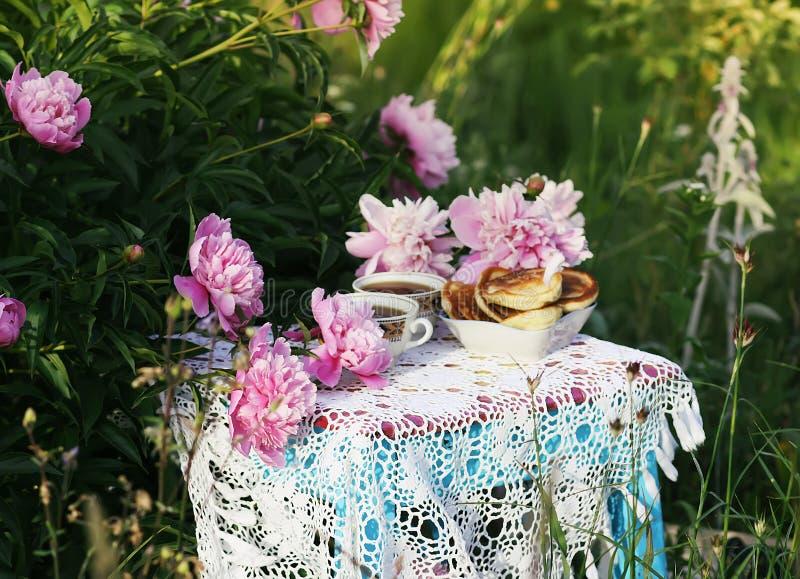 Thee in de stijl van het land in de zomertuin Twee koppen zwarte thee en pannekoeken op met de hand gemaakt gehaakt uitstekend ka stock foto's