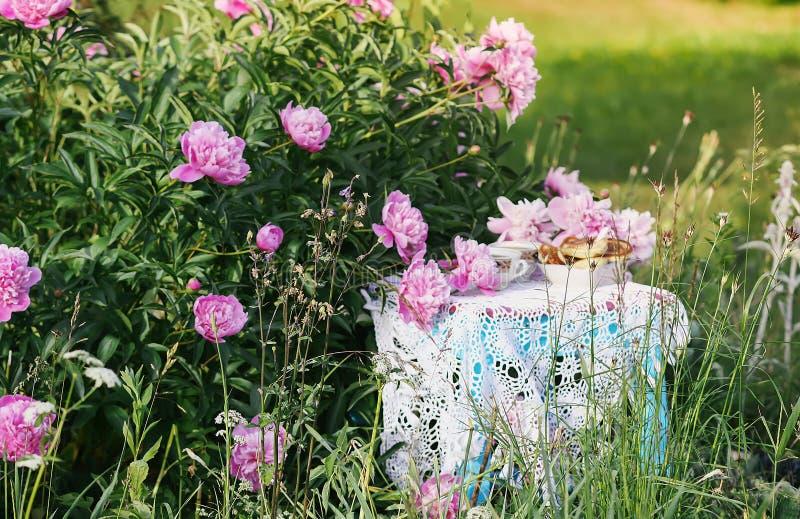 Thee in de stijl van het land in de zomertuin Twee koppen zwarte thee en pannekoeken op met de hand gemaakt gehaakt uitstekend ka stock fotografie
