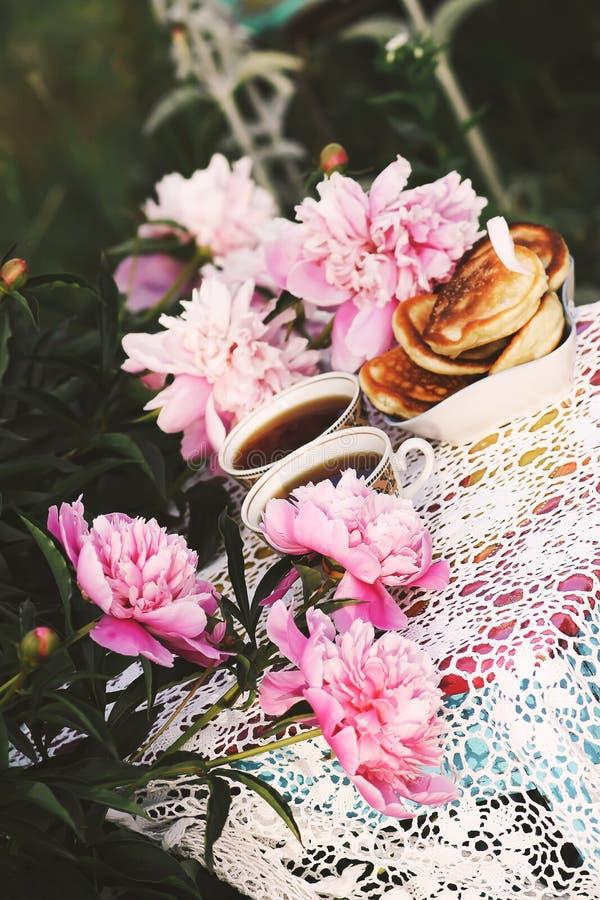 Thee in de stijl van het land in de zomertuin Twee koppen zwarte thee en pannekoeken op met de hand gemaakt gehaakt uitstekend ka stock afbeelding
