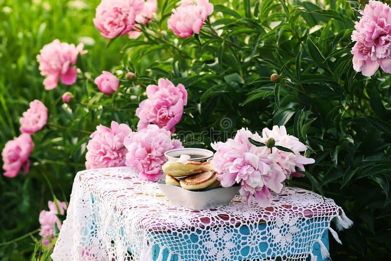 Thee in de stijl van het land in de zomertuin Twee koppen zwarte thee en pannekoeken op met de hand gemaakt gehaakt uitstekend ka stock afbeeldingen