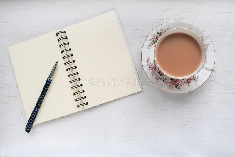 Thee in een uitstekende kop en een schotel, en notitieboekje met blanco pagina's royalty-vrije stock foto's