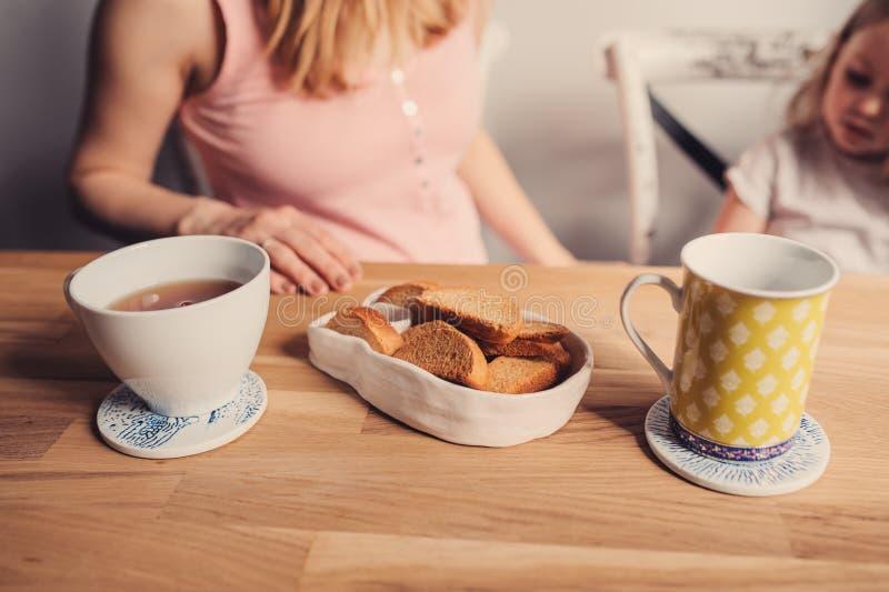 Thee en koekjes voor ontbijt op houten lijst met moeder en baby op achtergrond royalty-vrije stock fotografie