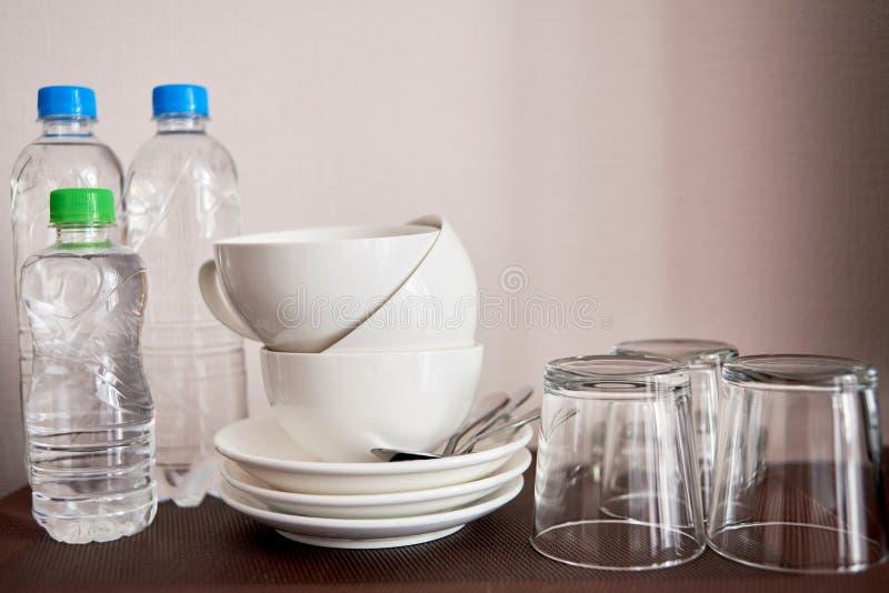 Thee en koffie die reeks in de ruimte van het luxehotel met schone koppen, glazen en flessen water, exemplaarruimte maken stock afbeelding