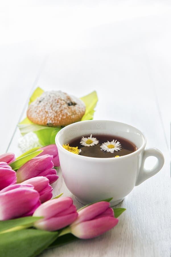 Thee en muffins met groene bakselkoppen met tulpen stock foto