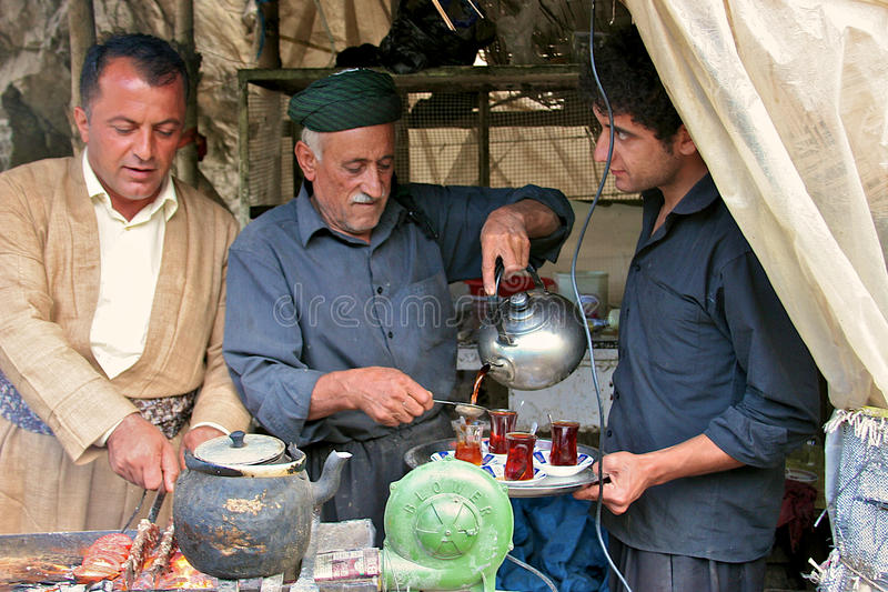 Thee het dienen en kebab het roosteren in kleine keet door weg. Irak. stock afbeelding