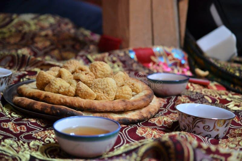 Thee het drinken in Centraal-Azië, Tadzjikistan, theeceremonie en gastvrijheid, bij een huwelijk in Tashkurgan Xinjiang stock afbeelding