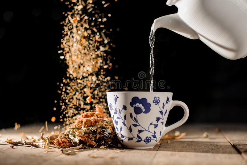 Thee het gieten van een witte theepot in het glas met een blauw patroon dichtbij het dalende handvol droge kruiden stock afbeelding
