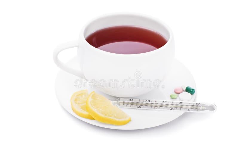 Thee met citroen, één of andere pillen en thermometer stock foto