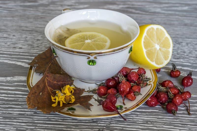 Thee met citroen in een witte kop Rode bessen op de lijst stock afbeelding