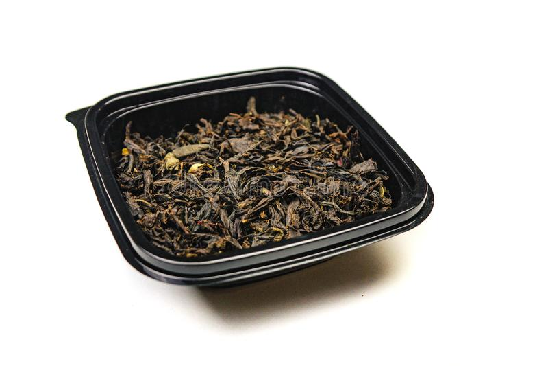 thee met droge bloemen en geglaceerd op een zwarte plaat Ge?soleerdj op witte achtergrond Sluit omhoog royalty-vrije stock afbeeldingen