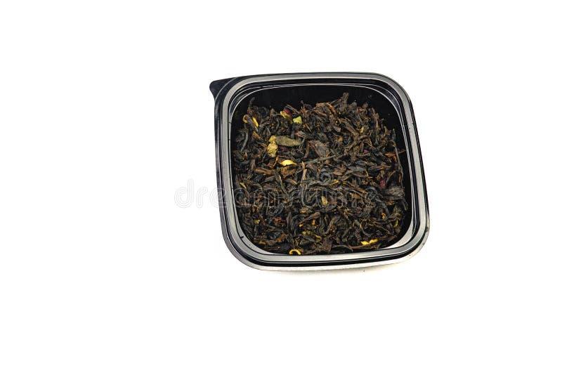 thee met droge bloemen en geglaceerd op een zwarte plaat Ge?soleerdj op witte achtergrond Sluit omhoog royalty-vrije stock fotografie