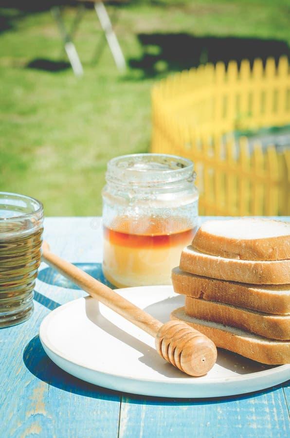 thee met honing en de plakken van besnoeiings witte gebakjes op een houten blauwe lijstachtergrond Thee met honing in een de zome royalty-vrije stock afbeelding