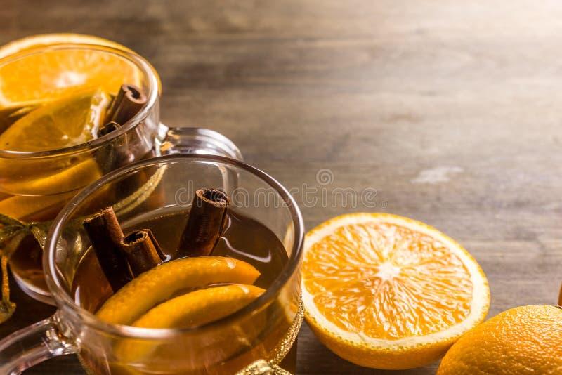Thee met sinaasappel en kaneel, sinaasappelen op smaak die wordt gebracht die stock foto's