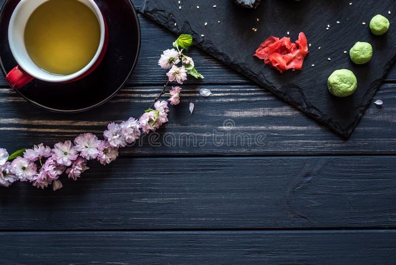 Thee, sakura, sushi op een zwarte achtergrond stock foto's