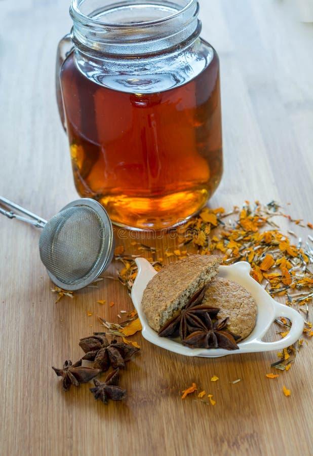 Thee, thee stainer, droge kaneel, veganistkoekjes en anijsplant op hout stock fotografie