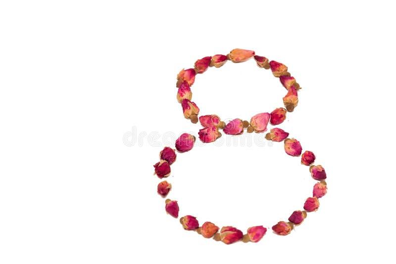 Thee van bloemblaadjes en rosebuds op de lijst in de vorm worden verspreid die stock afbeeldingen