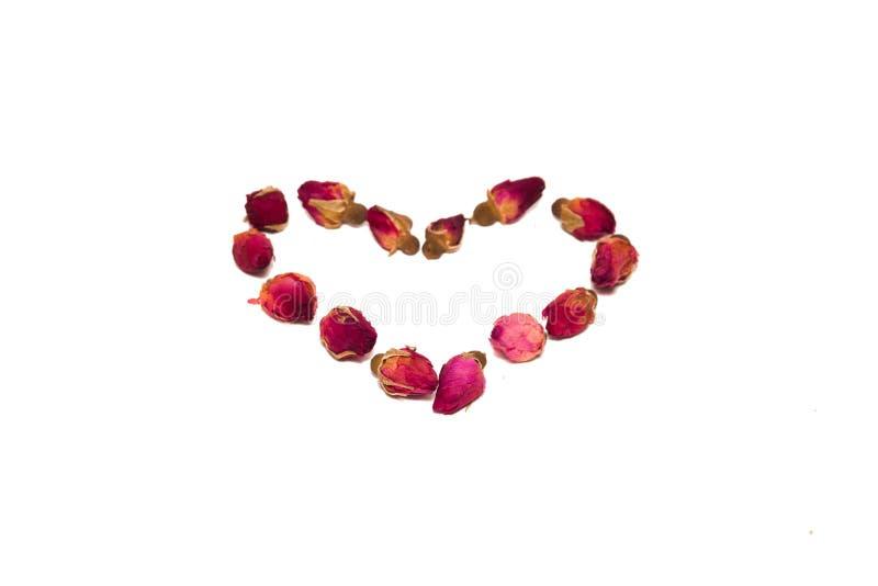 Thee van bloemblaadjes en rosebuds op de lijst in de vorm worden verspreid die royalty-vrije stock foto
