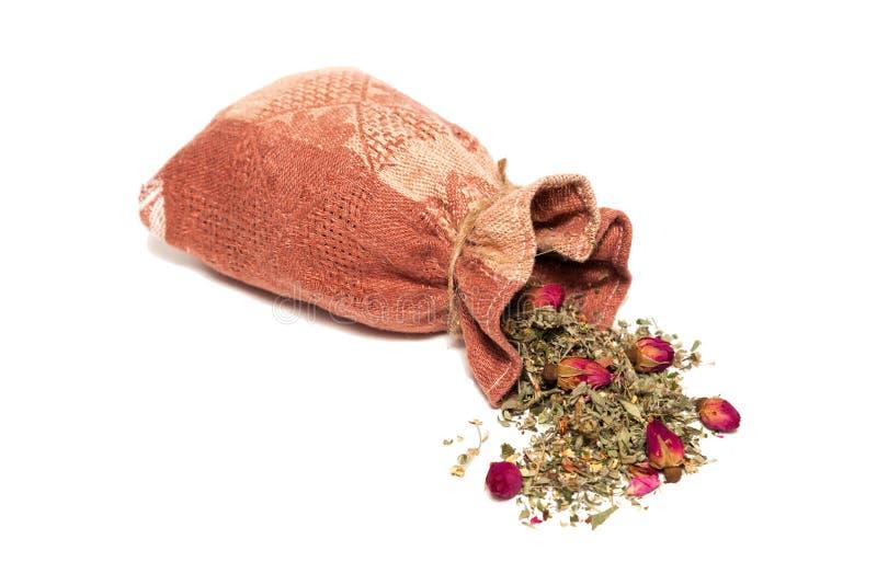 Thee van bloemblaadjes en rosebuds op de lijst van de zak worden verspreid die stock foto