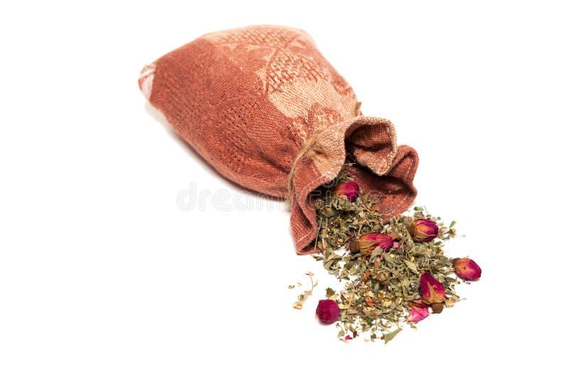 Thee van bloemblaadjes en rosebuds op de lijst van de zak worden verspreid die royalty-vrije stock fotografie