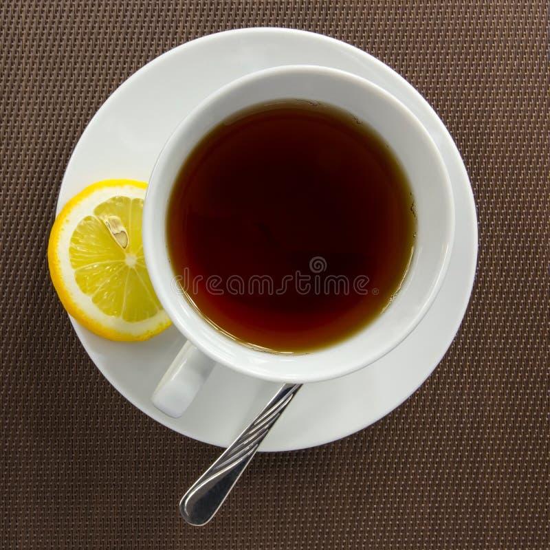Theekop en plak van citroen stock afbeeldingen