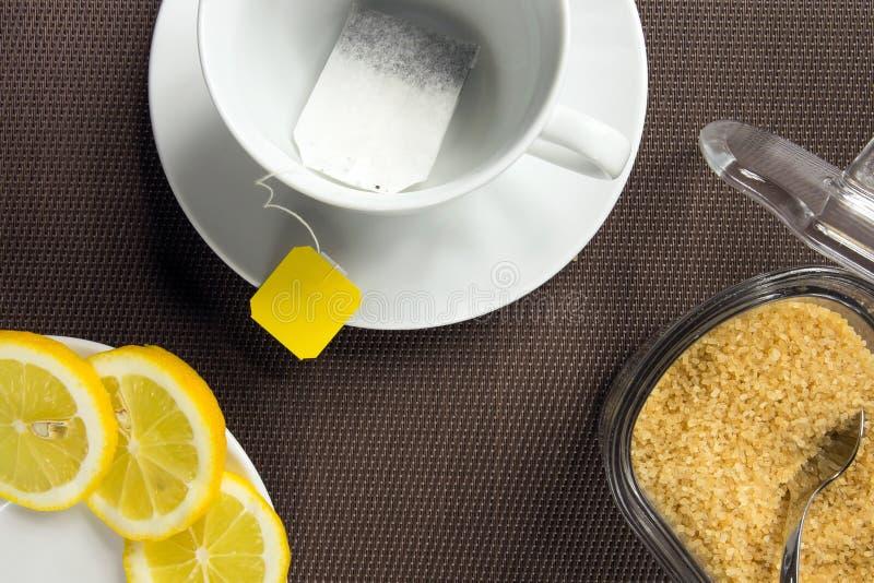 Theekop, plakken van citroen en bruine suiker stock afbeeldingen