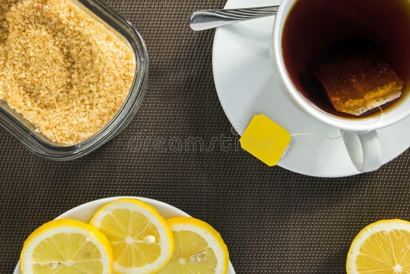 Theekop, plakken van citroen en bruine suiker royalty-vrije stock afbeelding