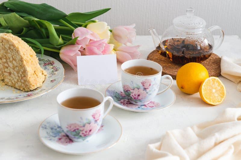Theekransje met eigengemaakte cake, citroen, theepot en tulpen op de achtergrond De ruimte van het exemplaar stock foto