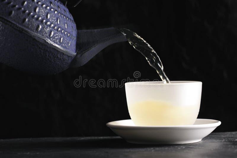 Theepot die groene thee poring in een kop stock foto's