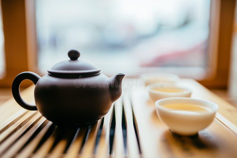 Theepot en koppen met Chinese thee op de lijst voor de theeceremonie stock afbeelding
