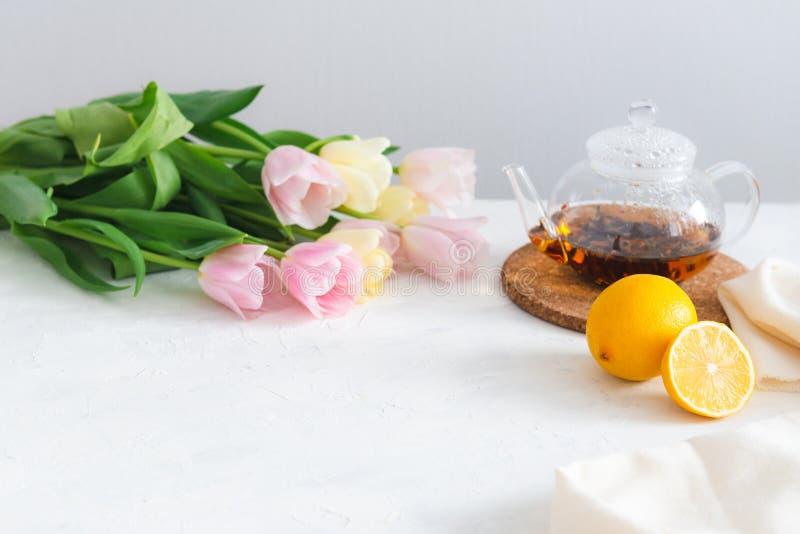 Theepot met zwarte thee, citroen en bloemen op witte lijst De ruimte van het exemplaar De lentetheekransje stock foto's