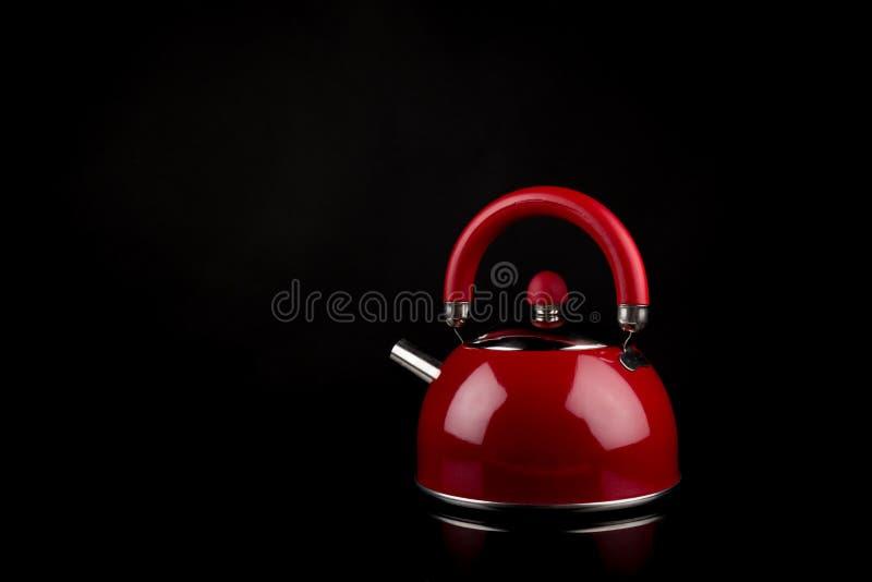 Theepot, Rode die staaltheepot op zwarte achtergrond met bezinningen wordt geïsoleerd De ruimte van het exemplaar stock foto's