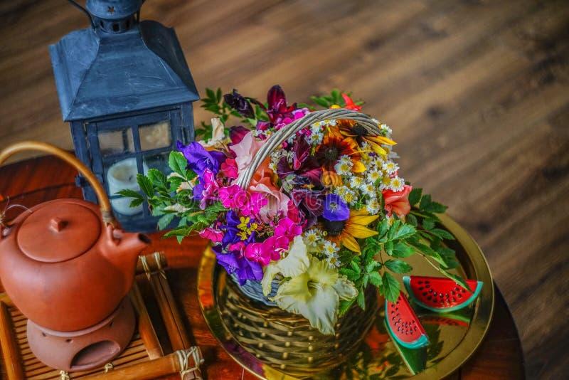 Theesamenstelling met bloemen en een mooie zwarte kandelaar op de achtergrond van een houten lijst en een houten vloer stock foto's
