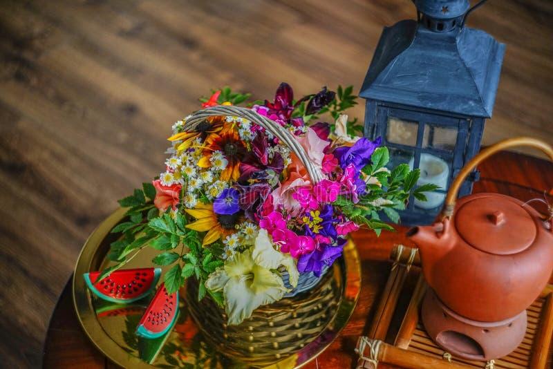 Theesamenstelling met bloemen en een mooie zwarte kandelaar op de achtergrond van een houten lijst en een houten vloer royalty-vrije stock afbeeldingen