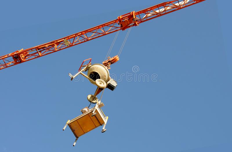 Cement mixer and circular saw, burglar proof. Theft protection, a crane with a hanging cement mixer and circular saw at construction site royalty free stock images