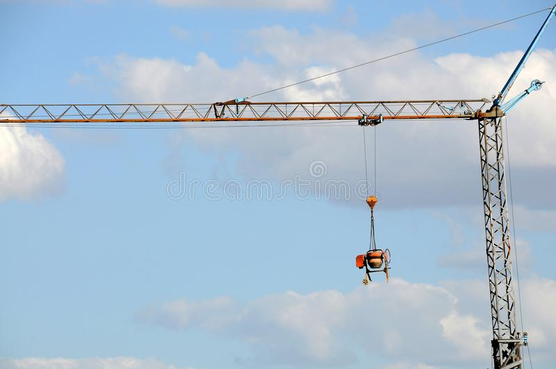Cement mixer, burglar proof. Theft protection, a crane with a hanging cement mixer at construction site royalty free stock images