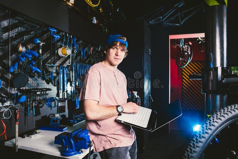 Thema bedrijfsberoepsmanager en technologie De jonge modieuze Kaukasische mannelijke winkel van de eigenaarfiets gebruikt een lap stock fotografie