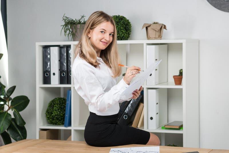 Thema bedrijfsvrouw op het werk Mooie jonge Kaukasische vrouwen het bedrijfsman werk zitting op de rand van de lijst in stock afbeelding