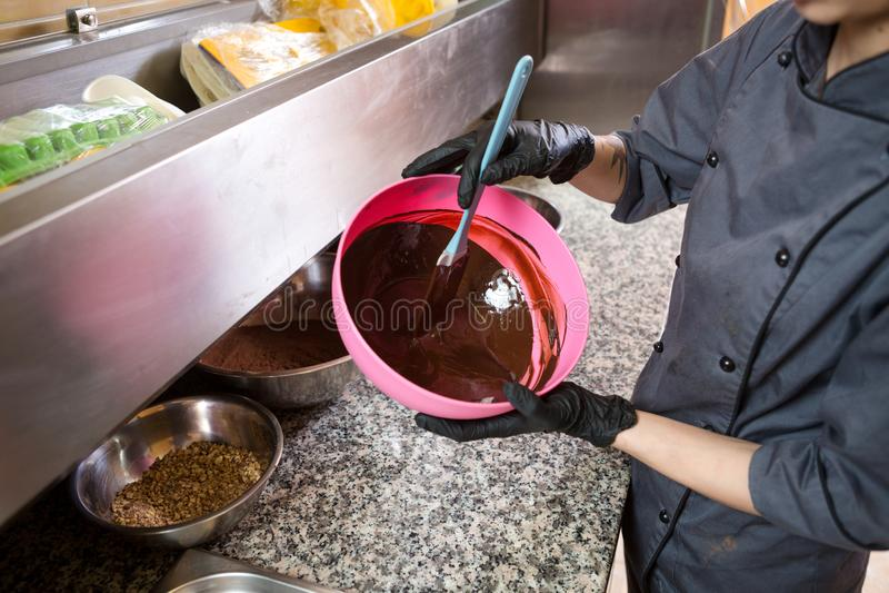 Thema, das Schokolade kocht Nahaufnahme einer Hand Junger kaukasischer Frauenkoch mit Tätowierung und in der Uniform bereitet vor stockfotografie
