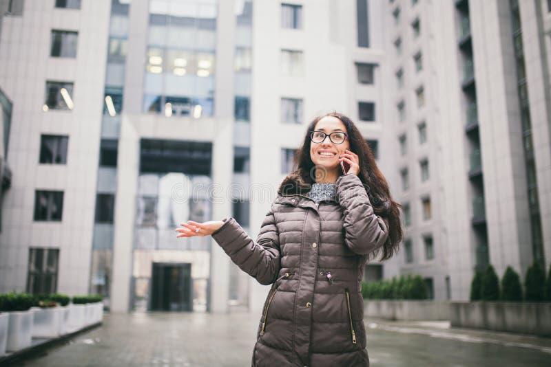 Thema ist die Geschäftslage Schöne junge Frau der europäischen Ethnie mit den tragenden Gläsern und Mantel des langen Brunettehaa lizenzfreies stockfoto