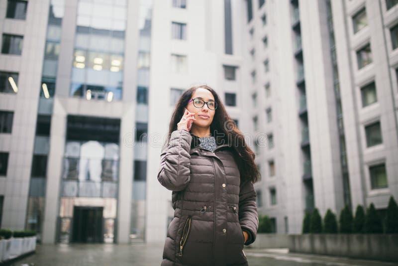 Thema ist die Geschäftslage Schöne junge Frau der europäischen Ethnie mit den tragenden Gläsern und Mantel des langen Brunettehaa stockbild