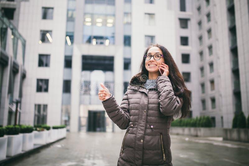 Thema ist die Geschäftslage Schöne junge Frau der europäischen Ethnie mit den tragenden Gläsern und Mantel des langen Brunettehaa stockfotografie